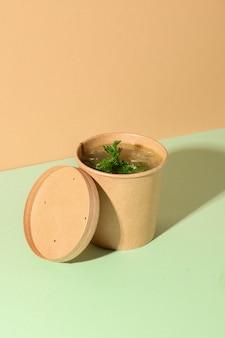 Gezonde kippenbouillon op bruin papier. verticaal formaat. creatieve minimale stijl.
