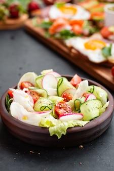 Gezonde klassieke plantaardige verse salade van sla, tomaat, komkommer, ui en sesam met olijfolie dressing op zwarte plaat en grijs.