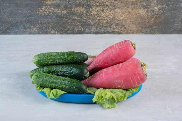 Gezonde komkommers en rode radijs op blauw bord. hoge kwaliteit foto