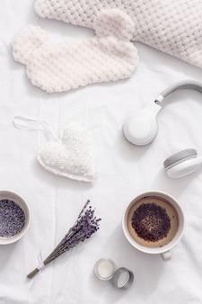 Gezonde lavendelkruiden thee in beker voor ontspanning voor het slapengaan. slaapmasker en balsem met etherische olie