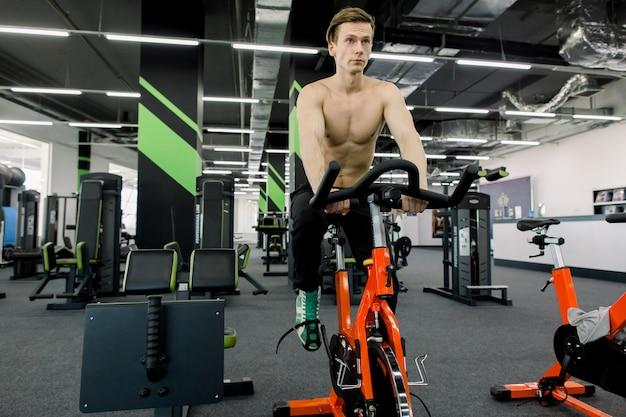 Gezonde levensstijl concept. de jonge sportieve mens zonder overhemd oefent fiets bij spinningklasse uit. cardio training. de jonge stationaire fiets van het sportpersonenvervoer in fitness gymnastiek.