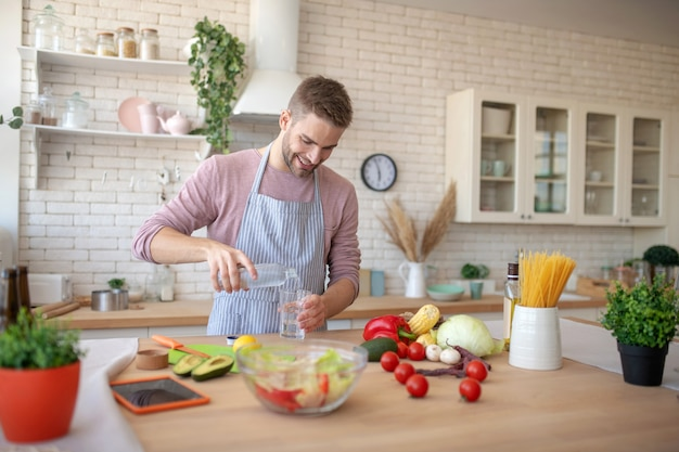 Gezonde levensstijl. een man die groenten eet en schoon water drinkt