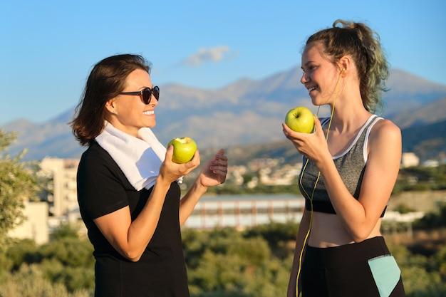 Gezonde levensstijl en gezond voedselconcept. glimlachende fitness moeder en tienerdochter samen appels eten, praten, rusten na atletisch hardlopen en buiten sporten