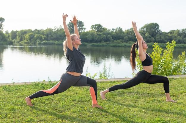Gezonde levensstijl en mensenconcept - flexibele vrouwen die yoga doen in het zomerpark