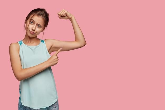 Gezonde levensstijl en sportconcept. ontevreden europese vrouw wijst naar armspier