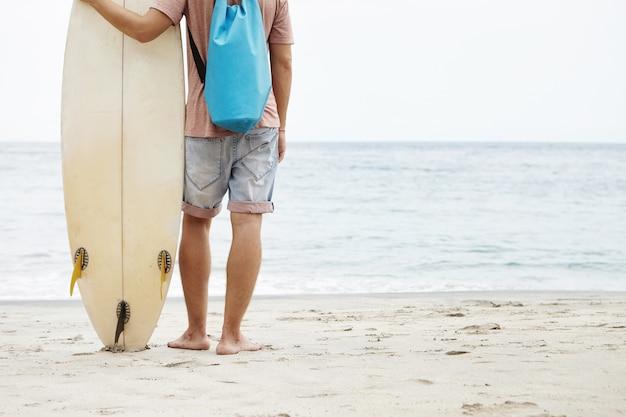 Gezonde levensstijl en vrije tijd concept. achterste bebouwde weergave van blanke toerist die op blote voeten op het zandstrand staat en witte surfplank vasthoudt, met uitzicht op de kalme en vredige oceaan