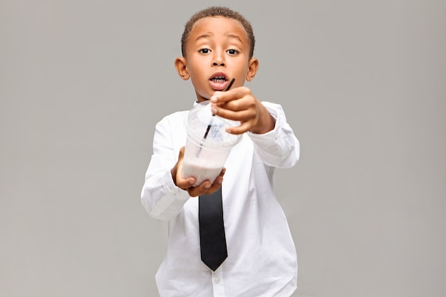 Gezonde levensstijl, eten, drinken en jeugdconcept. foto van emotionele opgewonden afro-amerikaanse schooljongen in uniform met plastic pot met fruitmilkshake, die je aanbiedt om wat te hebben