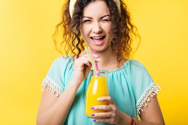 Gezonde levensstijl. evenwichtige voeding en welzijn. leuke jonge dame die een fles vers vruchtensap vasthoudt, glimlacht, knipoogt.