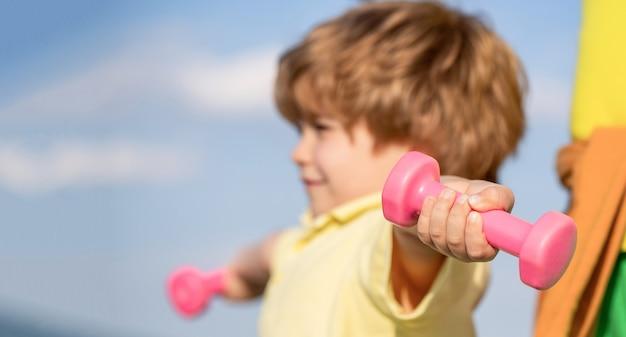 Gezonde levensstijl. fitness kind. kid trainen met halters. sporten voor kleine kinderen. sportieve jongen met halters. sport. fitness, gezondheid en energie. vrolijke jongen doet oefeningen met halters