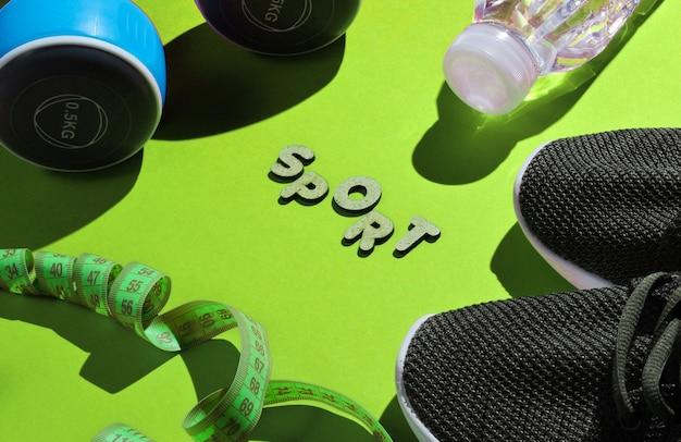 Gezonde levensstijl. halters, liniaal, fles water, sneakers op groen met woordsport