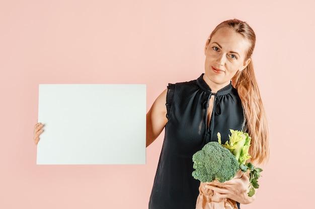 Gezonde levensstijl. het meisje houdt broccoli en groene groenten in haar handen, roze muur. dieet en goede voeding. .