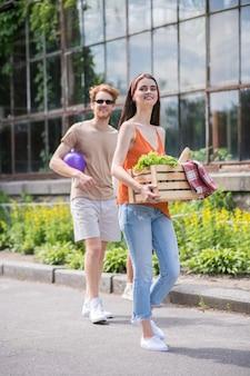 Gezonde levensstijl. jonge vrolijke man met bal en langharig meisje met eten dat op zonnige dag in het park gaat picknicken