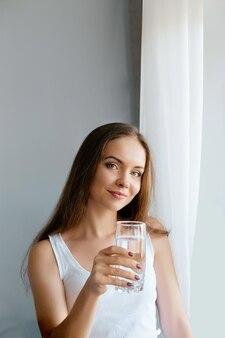 Gezonde levensstijl. jonge vrouw drinken uit een glas vers water