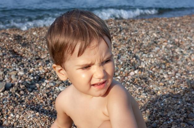 Gezonde levensstijl. kleine jongen rust en plezier op een rotsachtig strand aan de middellandse zeekust