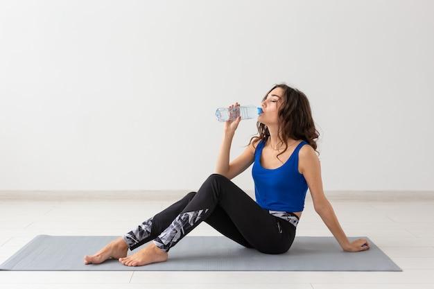 Gezonde levensstijl, mensen en sport concept - jonge mooie vrouw beoefenen van yoga en drinkwater