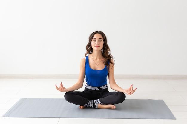 Gezonde levensstijl, mensen en sport concept - jonge vrouw met krullend haar doet yoga over wit oppervlak.