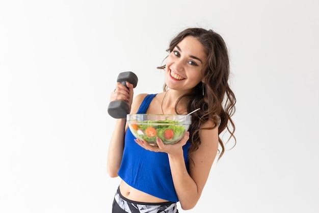 Gezonde levensstijl, mensen en sport concept - portret van een gezonde vrouw met groenten en halters.