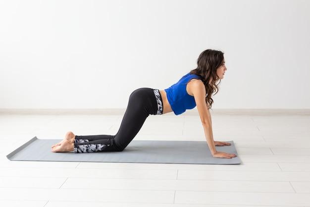 Gezonde levensstijl, mensen en sportconcept. jonge vrouw met krullend haar die yoga op wit doet.