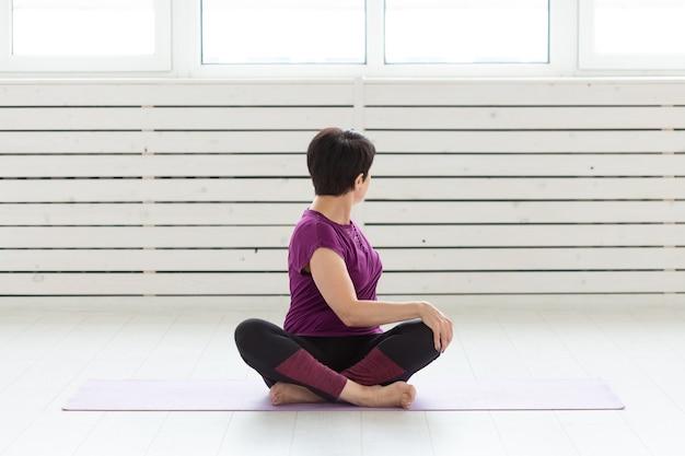 Gezonde levensstijl, mensen en sportconcept. vrouw van middelbare leeftijd die yoga doet.