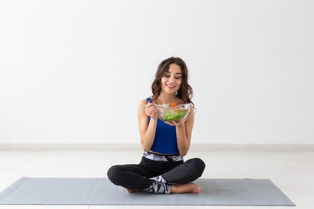 Gezonde levensstijl, mensen en sportconcept - yogavrouw met een kom groentesalade.