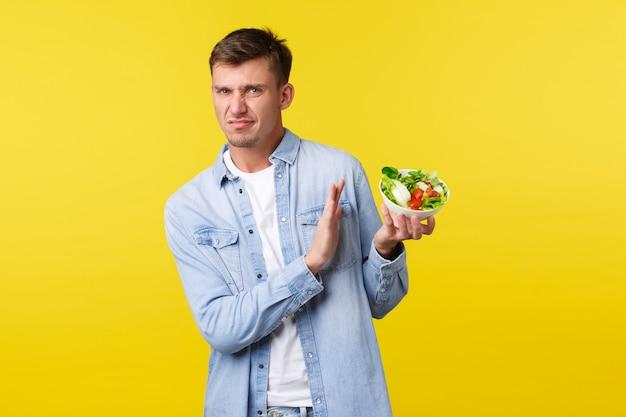 Gezonde levensstijl, mensen en voedselconcept. weerzinwekkende en teleurgestelde blonde man die grijnst van afkeer en weigert te bowlen met salade, houdt er niet van om op dieet te blijven, gele achtergrond.