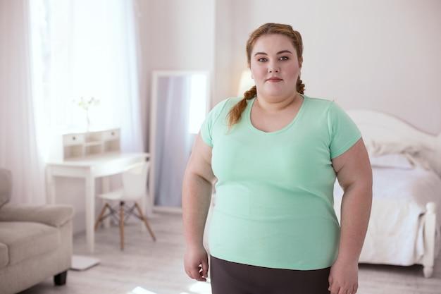 Gezonde levensstijl. mollige jonge vrouw, gekleed in sportkleding staande in de kamer