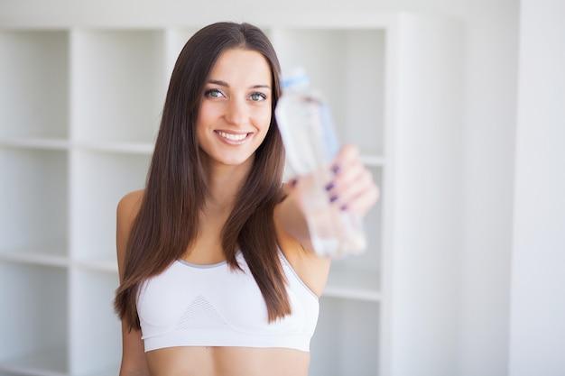 Gezonde levensstijl. mooie geschikte jonge vrouw die een fles water houdt