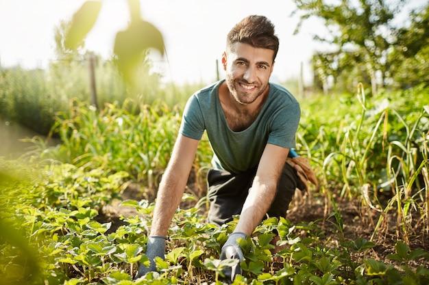 Gezonde levensstijl. plattelandsleven. close-up buitenshuis portret van jonge aantrekkelijke bebaarde blanke boer glimlachen, ochtend besteden in de tuin in de buurt van huis, gewas plukken