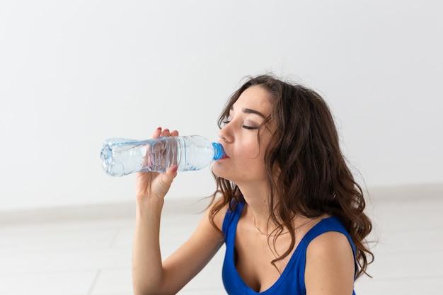 Gezonde levensstijl, sport, mensenconcept - jong vrouwen drinkwater na het sporten.