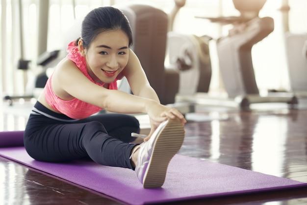 Gezonde levensstijl, sportieve vrouwelijke opwarmingsoefening die benen uitrekt vóór opleidingsfitness