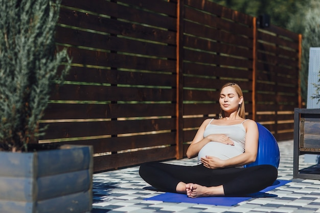 Gezonde levensstijl tijdens de zwangerschap. een zwanger meisje mediteert in lotushouding