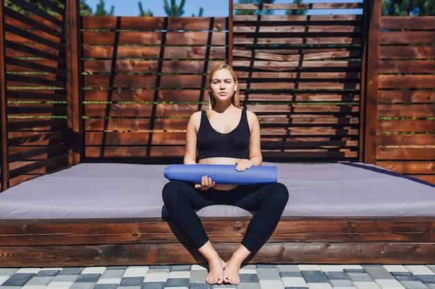 Gezonde levensstijl tijdens de zwangerschap jonge, mooie zwangere vrouw die mediteert op yogamatten in haar handen in de frisse lucht onder de zon