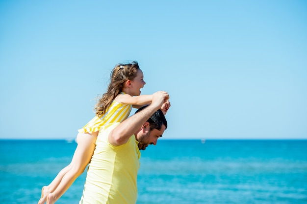 Gezonde liefhebbende vader en dochter samen spelen op het strand aan zee. gelukkig plezier lachende levensstijl. familievakantie op zee met een kind.