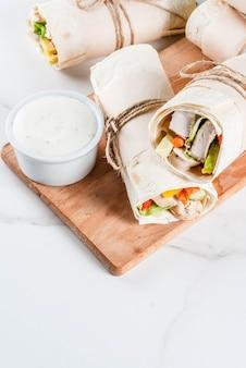 Gezonde lunch snack. stapel mexicaanse fajita-tortillaomslagen van het straatvoedsel met de geroosterde filet van de buffelskip en verse groenten