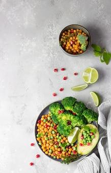 Gezonde lunch van broccoli, kikkererwten, avocado, doperwtjes, granaatappel, limoen en munt