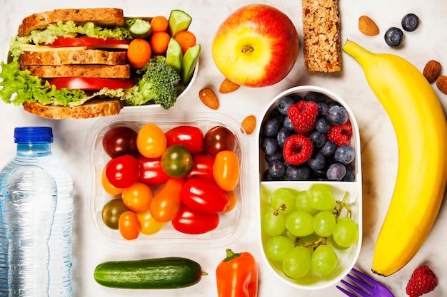 Gezonde lunchbox met sandwich en verse groenten, fles