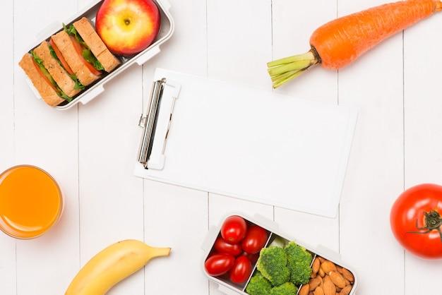 Gezonde lunchboxen met sandwich, verse groenten, fruit en noten op witte houten achtergrond. van bovenaanzicht