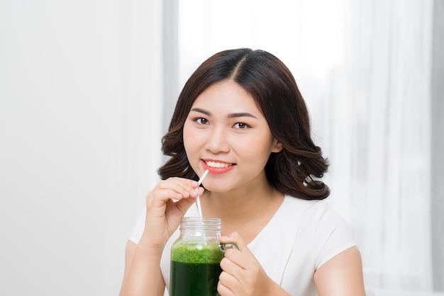 Gezonde maaltijd. gelukkige mooie lachende vrouw die groene detox groentesmoothie drinkt. gezonde levensstijl, voeding en eten. drink sap. dieet, gezondheid en schoonheidsconcept.