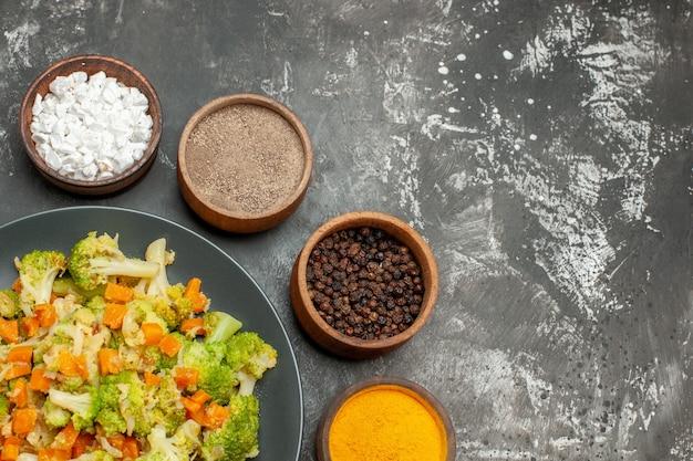 Gezonde maaltijd met brocoli en wortelen op een zwarte plaat en kruiden op grijze lijst