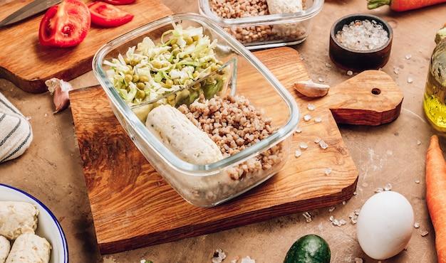 Gezonde maaltijdvoorbereidingscontainers met zelfgemaakte kippenworsten, boekweit en groentesalade op rustieke achtergrond. dieet, gewichtsverlies concept. selectieve focus
