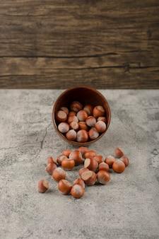 Gezonde macadamia noten in de dop op een stenen oppervlak.