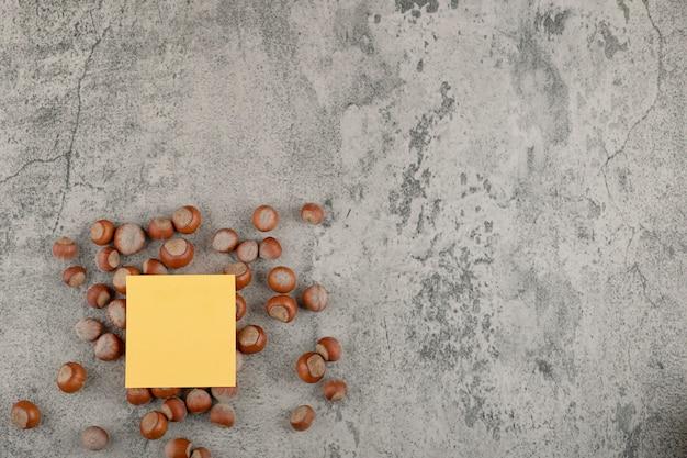 Gezonde macadamia-noten met gele vierkante sticker op een steenachtergrond.