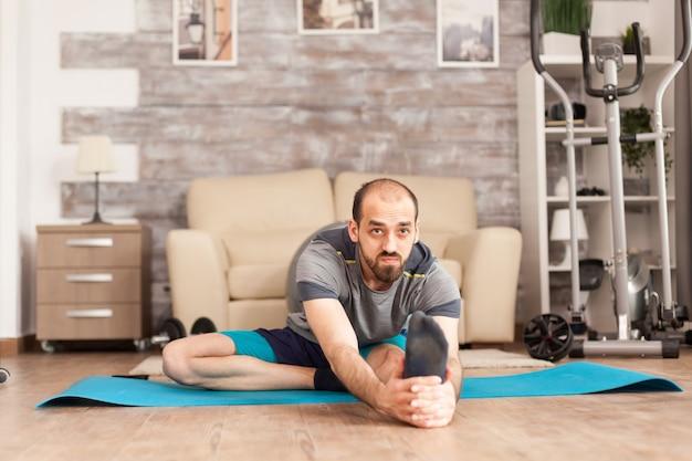 Gezonde man doet mobiele oefening op yogamat thuis tijdens wereldwijde pandemie.