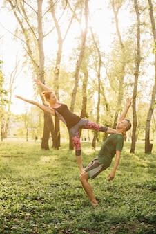 Gezonde man en vrouw die acroyoga in park doen