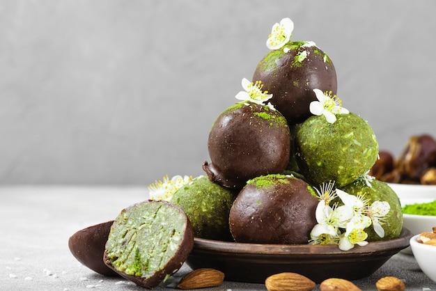 Gezonde matcha gelukzalige energieballen in chocoladeglazuur met bloemen, dadels, kokos en noten. veganistisch snackdessert. detailopname