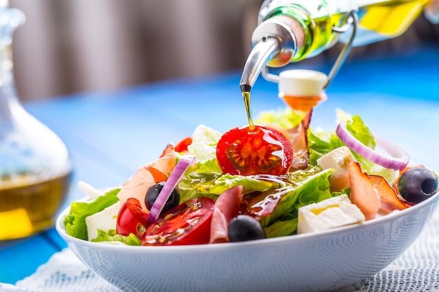 Gezonde mediterrane salade olijven tomaten parmezaanse kaas en prosciutto gieten olijfolie