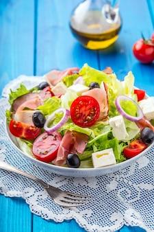 Gezonde mediterrane salade olijven tomaten parmezaanse kaas en prosciutto