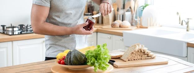Gezonde mensen preaparing ontbijtsandwich in keuken thuis