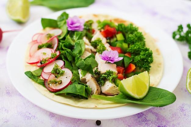 Gezonde mexicaanse maistaco's met gekookte kipfilet, spinazie, radijs en paprika.