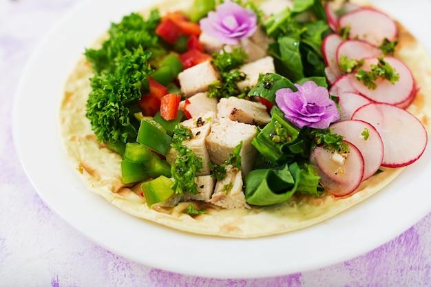 Gezonde mexicaanse maistaco's met gekookte kipfilet, spinazie, radijs en paprika